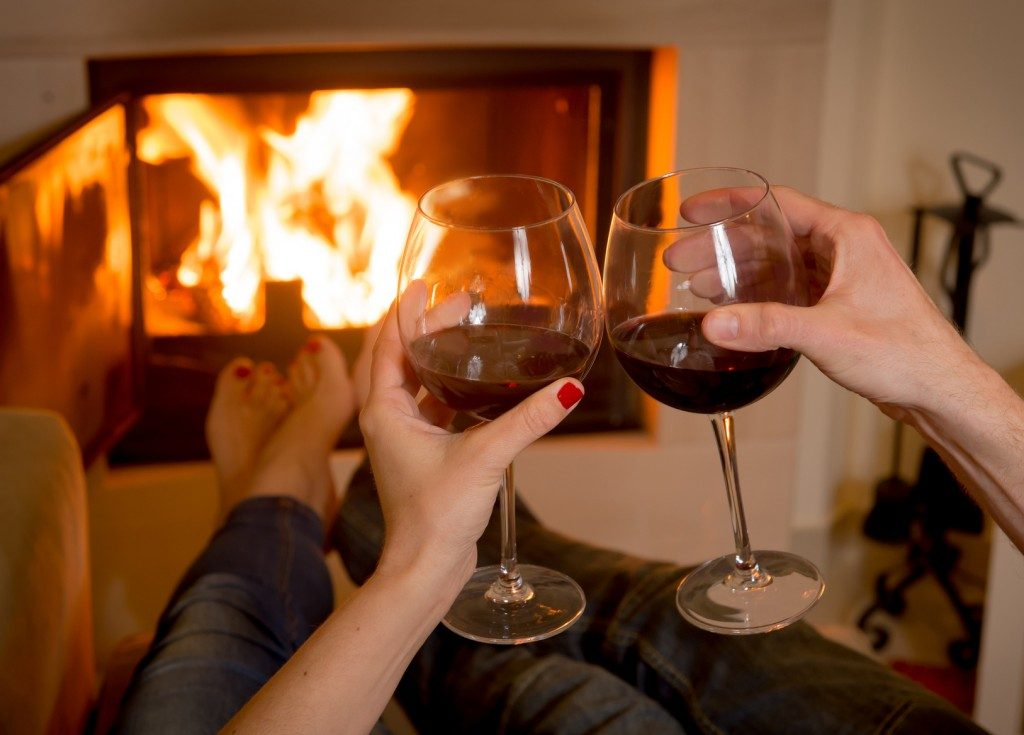 romantic couple drinking wine infront of fireplace fake fire hotel room idea